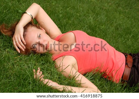 The girl lies on a grass and enjoys rest