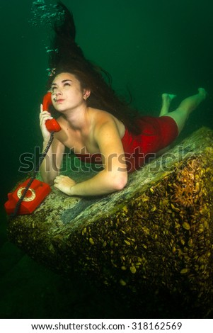 The girl lies on the bottom of the lake and chatting on the phone - stock photo