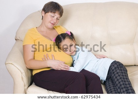 The girl listens to a stomach of mother - stock photo