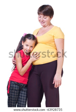 The girl listens to a stomach of mother, white background - stock photo