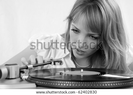 The girl listens to a vinylic disk black-and-white