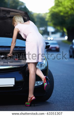 The girl looks at a car engine