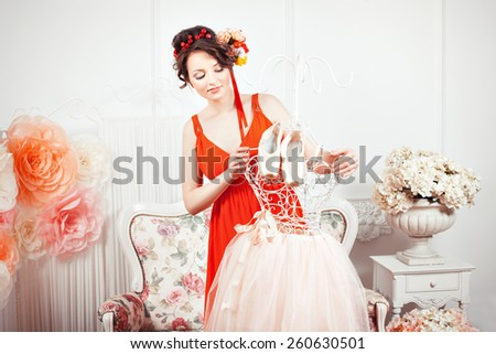The girl looks at tutu and ballet pointe shoes. Her hair decorated with flowers. - stock photo