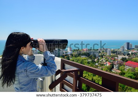 The girl looks in binokol at the city  - stock photo