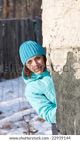 The girl looks out from round the corner - stock photo