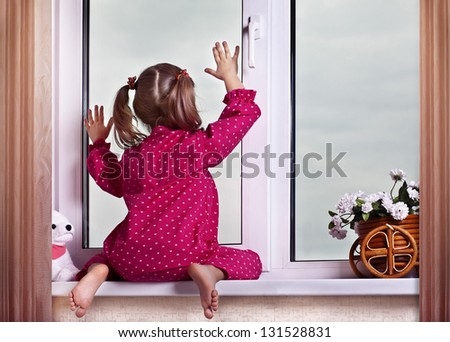 The girl looks out of the window - stock photo