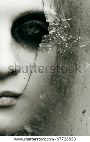 the girl looks through the broken glass - stock photo