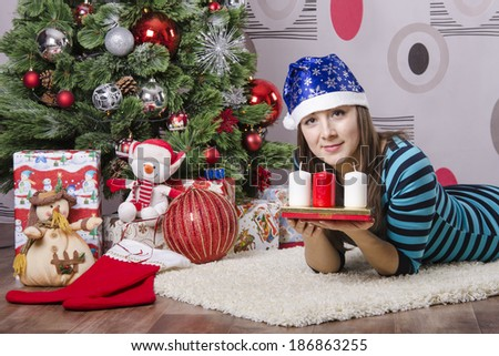 The girl lying on the carpet around the Christmas tree. A girl holding a candle and looks in a frame