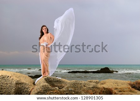 The girl near a stormy sea in fabrics - stock photo