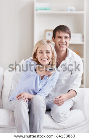 The girl next to a man switches TV channels - stock photo