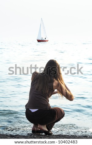 The girl on a coast and a sailing boat in the sea