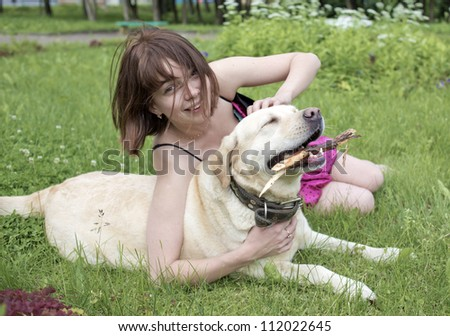 The girl on a lawn plays with a dog - stock photo