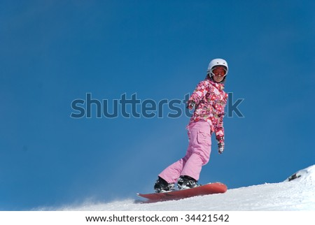 The girl on a snowboard at mountain top on a background of blue sky - stock photo