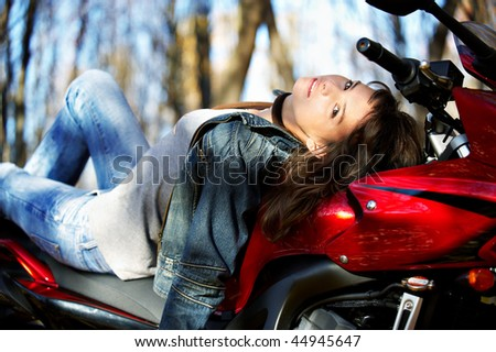 The girl on a stylish red motorcycle