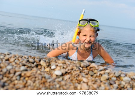 The girl on seacoast flounders about in water. In a mask, flippers and with a snorkel