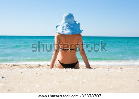 The girl on the beach wearing a hat - stock photo