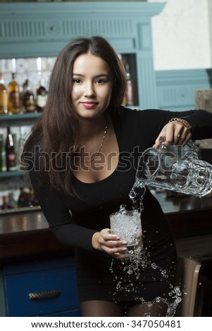 The girl on the blurry background poured from a carafe into a glass with ice water - stock photo