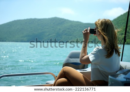 the girl on the boat photographs a landscape - stock photo
