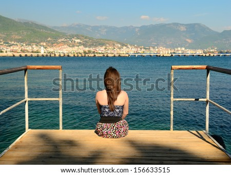 The girl on the pier sitting back and looking into the distance - stock photo