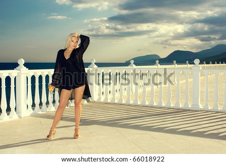 The girl on the sea with a wine glass looks at mountains - stock photo
