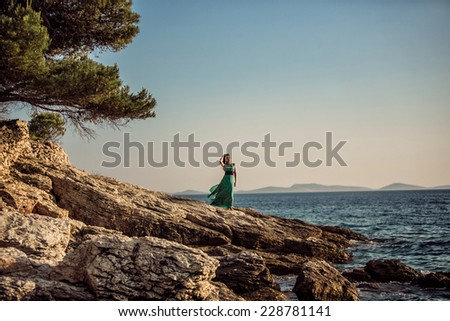 The girl on the shore of the sea in the green dress surrounded by rocks and trees