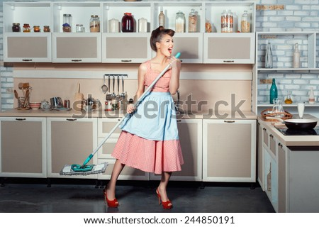 The girl opened her mouth much because when she sings cleans the kitchen. She carried a mop for washing floors. - stock photo