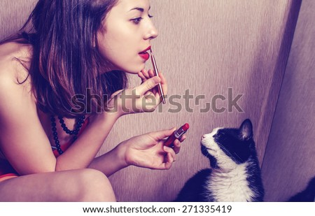 The girl paints lips with lipstick looking in the mirror and watching her cat. - stock photo