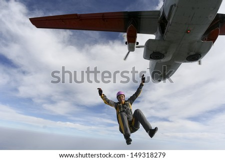 The girl parachutist jumps out of an airplane. - stock photo