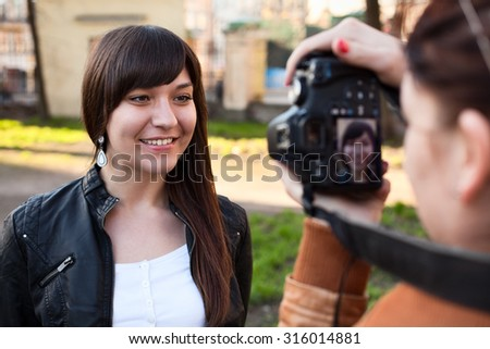The girl photographer photographing the model in outdoors - stock photo