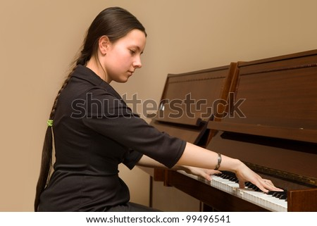 The girl playing the piano at the music school's office - stock photo