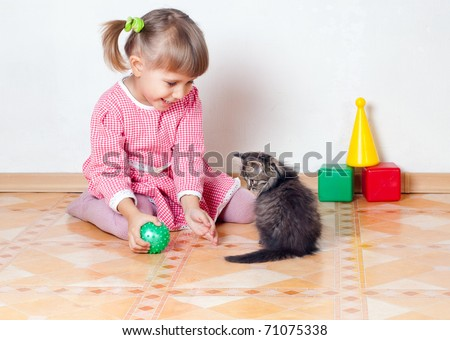 The girl plays with a kitten, an interior - stock photo