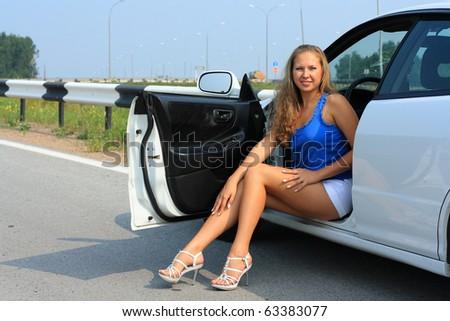 The girl poses near the car - stock photo