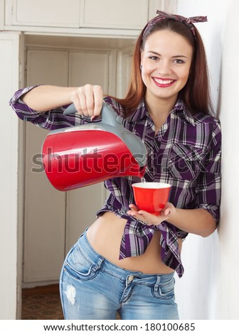 The girl pours water from the kettle into a cup - stock photo