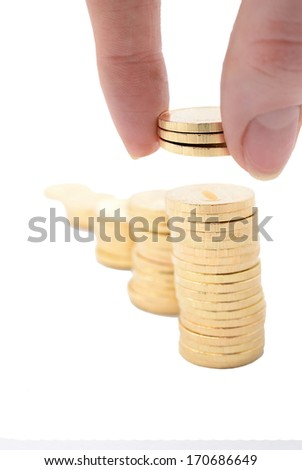 The girl puts coins a pyramid. Isolate on white  - stock photo