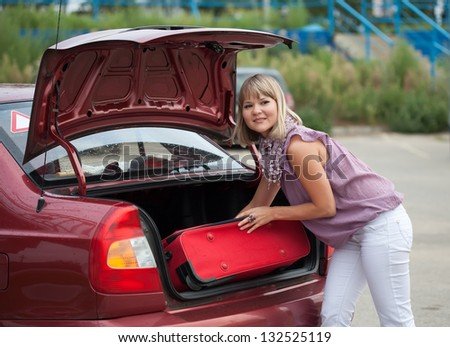 The girl puts the suitcase in the trunk of car - stock photo
