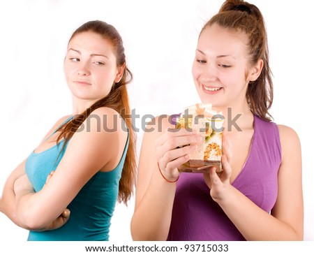 The girl received a gift, and the other girl looks with envy - stock photo