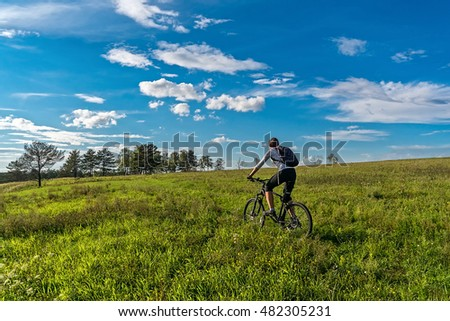 The girl rides a bicycle on a green meadow, summer day
