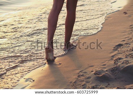 The girl runs barefoot along the sandy beach of the sea. Photo toned in the style of instagram