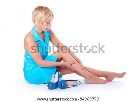 The girl's feet hurt, white background - stock photo
