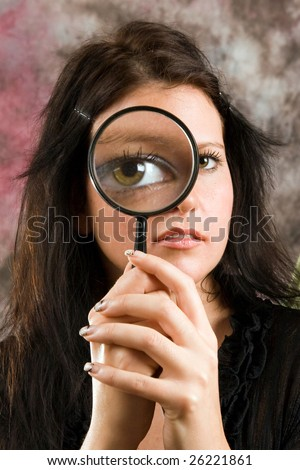 The girl searches for something through a magnifier - stock photo