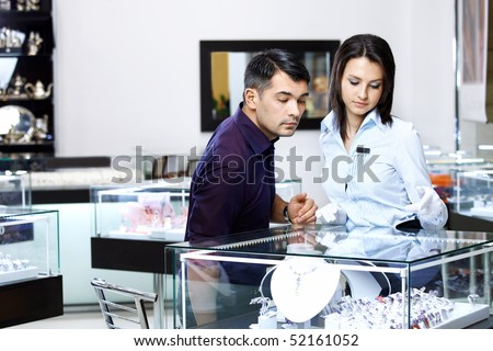 The girl-seller shows to the visitor assortment in jeweller shop - stock photo