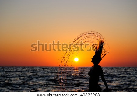 The girl sharply lifts wet hair from water. Decline. Silhouette. - stock photo