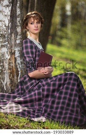 The girl sits at a birch with the book - stock photo