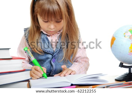 The girl sits at a table and writes to writing-books - stock photo