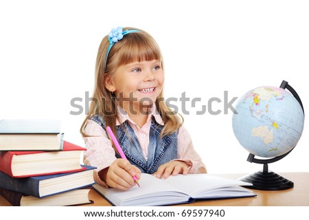 The girl sits at a table and writes to writing-books. Globe on table. Photo Isolated over white - stock photo