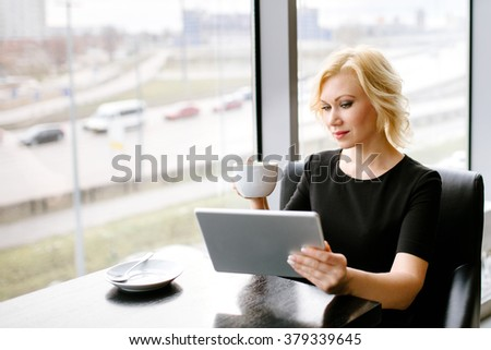 The girl sits at a table, has coffee and holds the tablet computer
