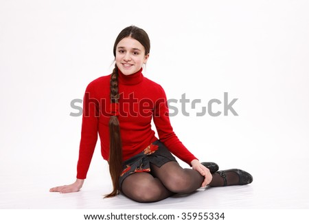 The girl sits having drawn in knees and smiles