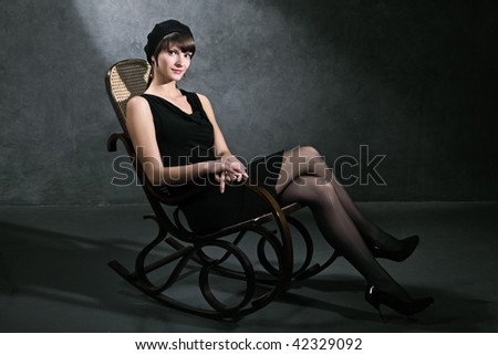 The girl sits in an armchair against a dark wall