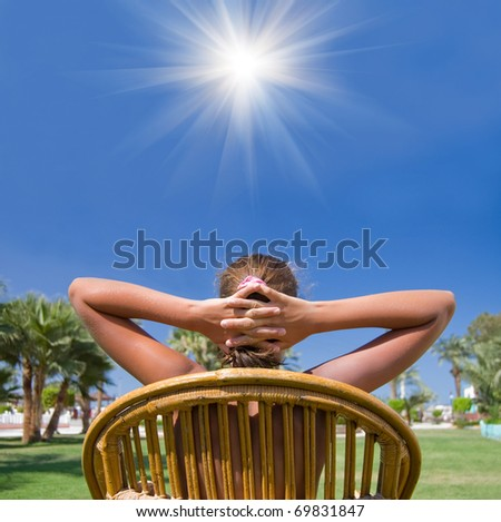 The girl sits in an armchair on a grass - stock photo