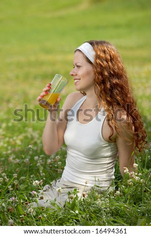 The girl sits on a background of a green lawn and drinks juice